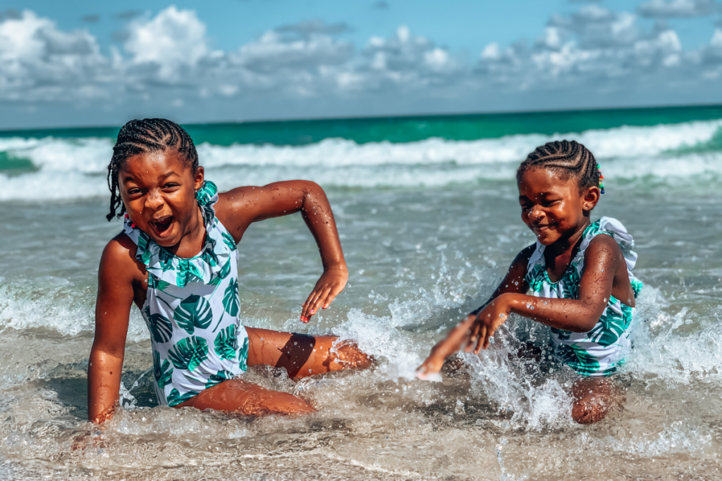 two little girls splash in the ocean water having a good time in south florida during fall