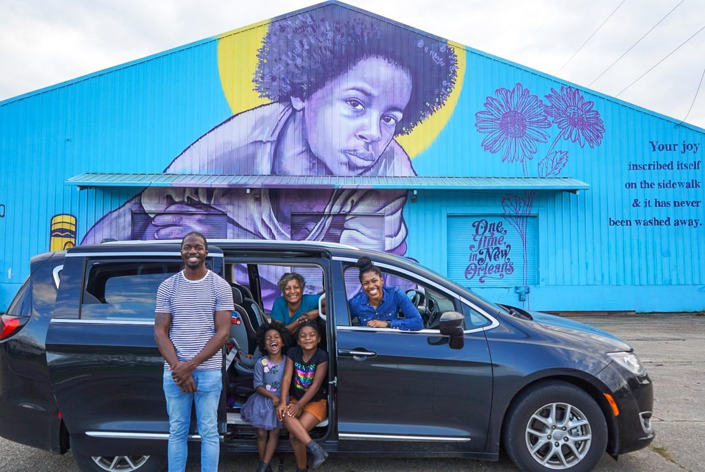 A family setting out on a road trip posing for a picture in front of their van getting ready to go for a drive.