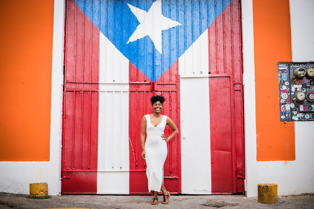 woman standing in front of a memorial of Puerto Rico's flag smiling contently enjoying her vacation to san juan without a passport