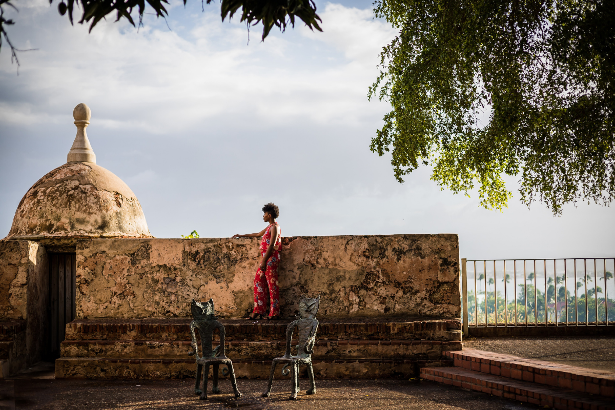 Woman standing along an aged wall in a courtyard in puerto rico.