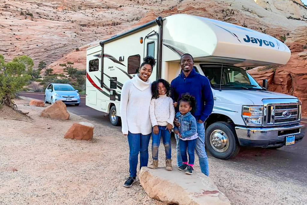Family standing outside of their RV on a dessert road trip smiling at the camera.