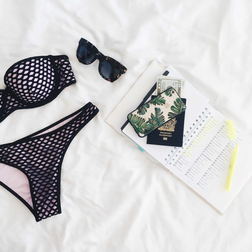 A bikini with a passport and money and a notebook with things to pack for traveling.