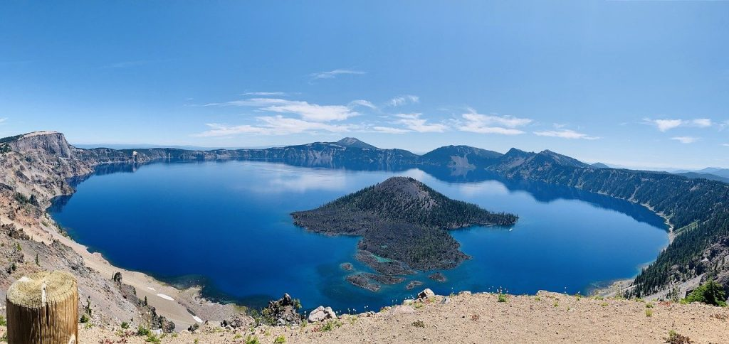 Crater lake national park part of the volcanic legacy scenic byway in Oregon. It is a beautiful lake with an island in the center surrounded by blue waters and rocky landscape.