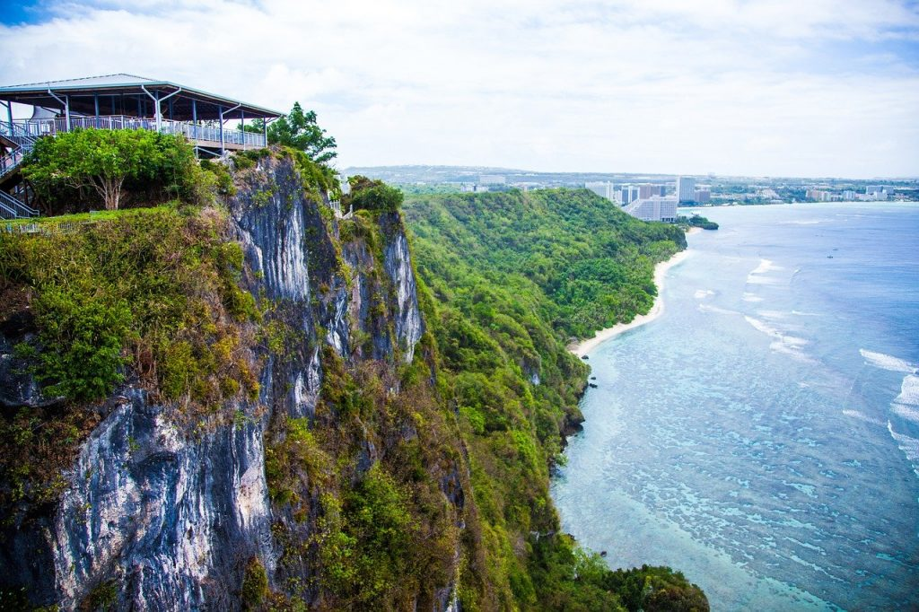 Guam cliff over looking the ocean with a vacation rental sitting on top of it with a scenic view of the city off in the distance.