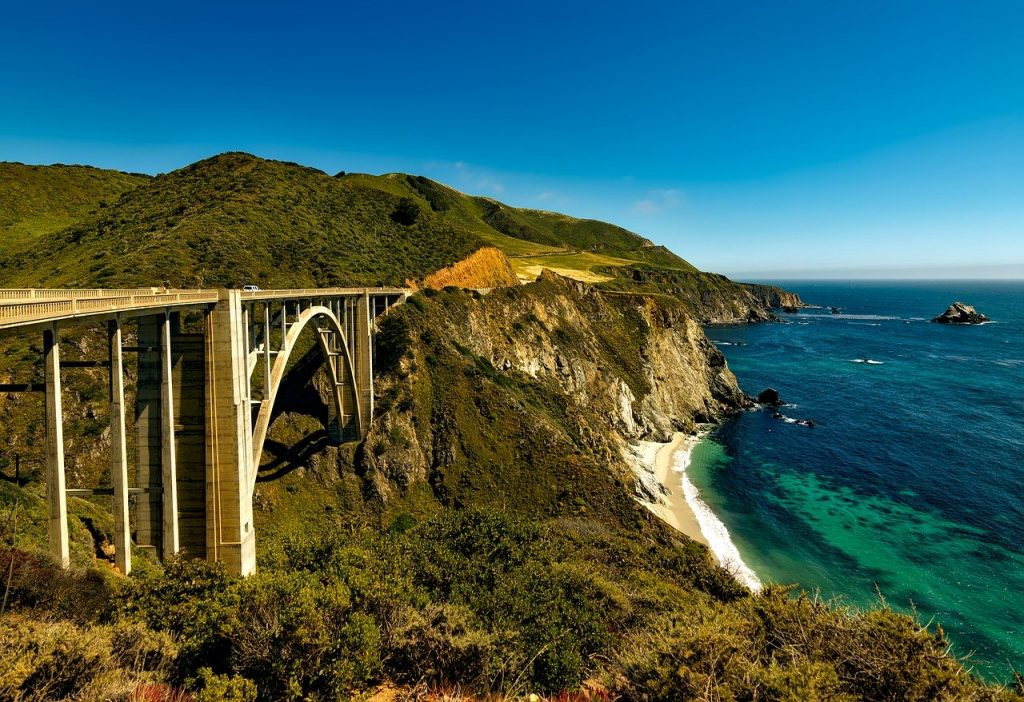 The pacific coast highway winding through a sea side cliff, showing a bridge and beautiful blue-green ocean water being one of the most amazing places to drive in the US.