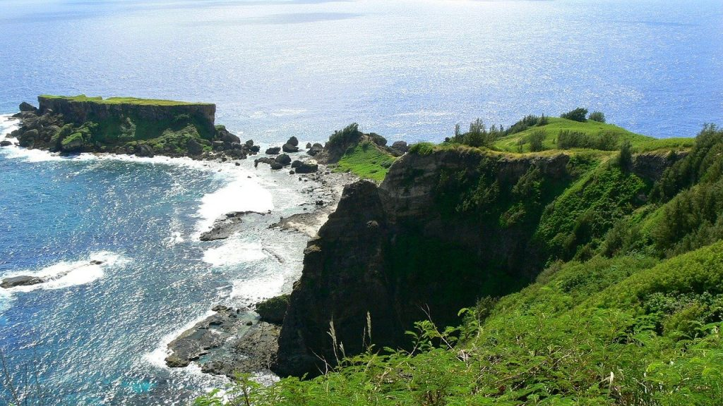 Saipan landscape part of the northern Mariana Islands with a rocky cliff showing teal ocean water. One of many places you can visit without a passport.