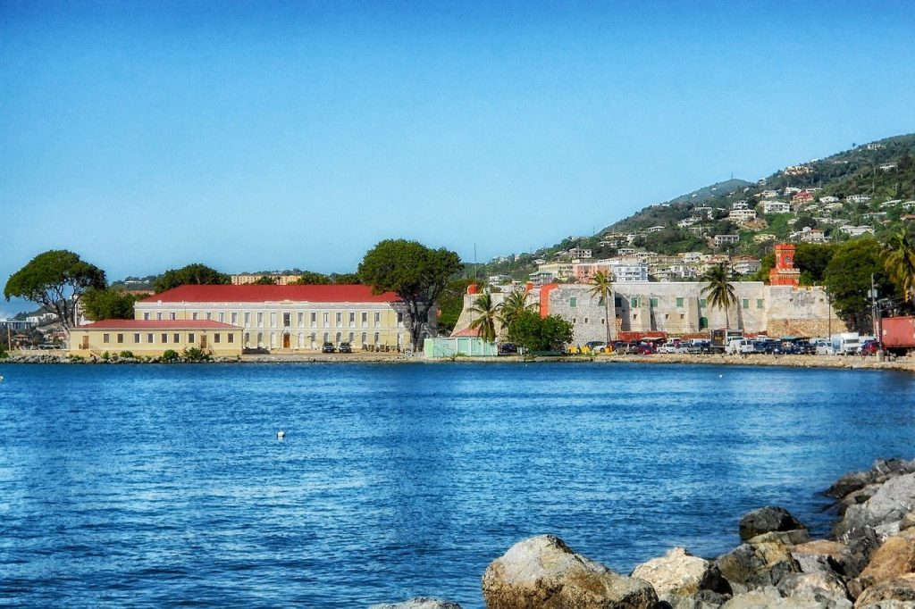 St. Thomas US  Virgin Island feature a picture of a bay with a rocky shore with  buildings along the coastline. The perfect place to go without a passport.