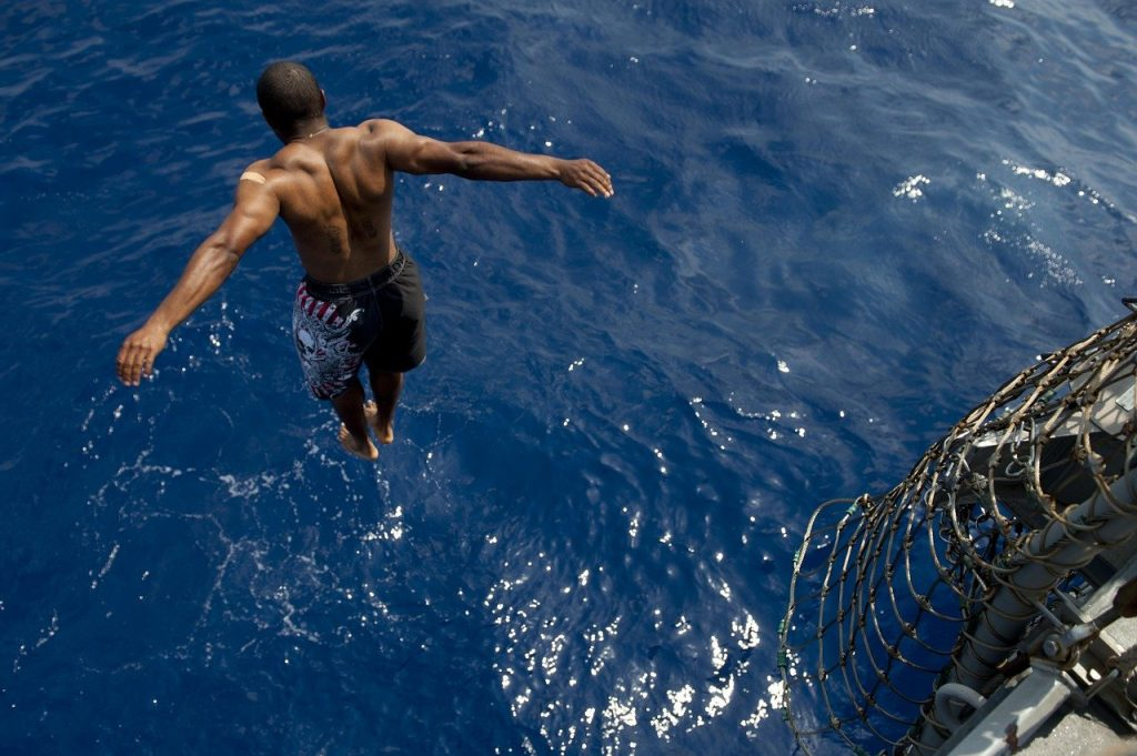 A man jumping off a boat into the ocean to swim in the Caribbean sea