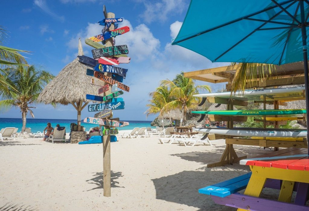 A sign sitting in the white sand on Curacao Island with the blue ocean in the background in the middle of hurricane season with blue skies and not a storm in site.