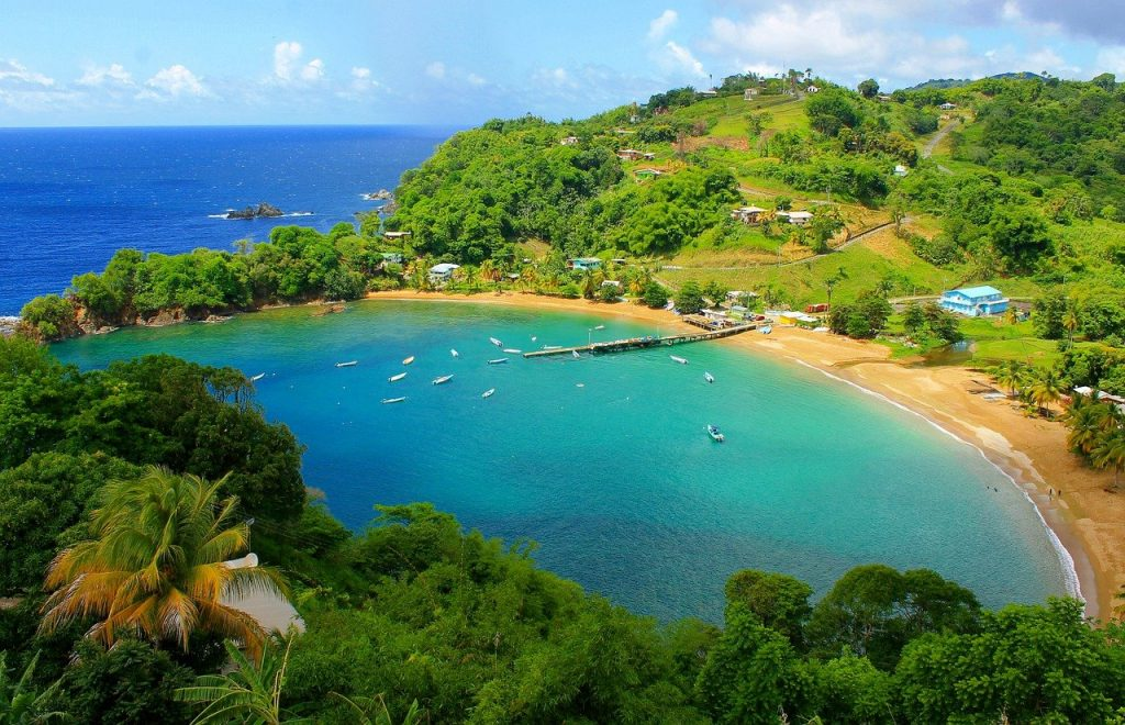 A bay in Tobago with blue waters a few boats and lush greenery all around.