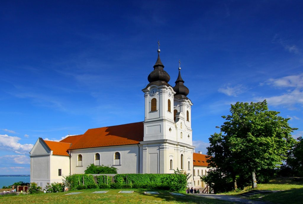 Tihany Abbey in Hungary sits on a hill with lush green grass and a clear blue sky.