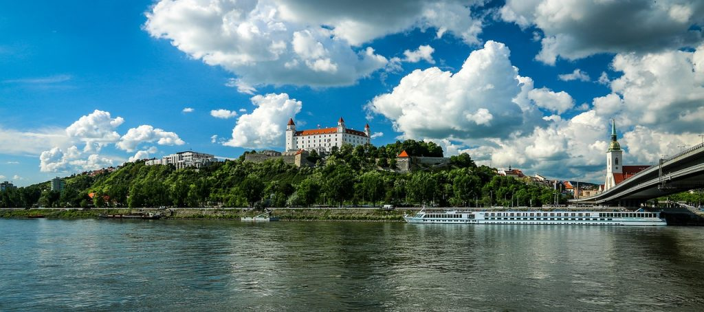 Bratislava, Slovakia. River view of the city with a boat floating through the cannel.