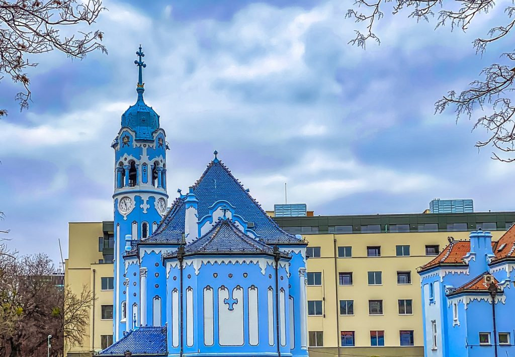Wood church in slovkia, blue buildings with white accents stand out from the modern day buidlings.