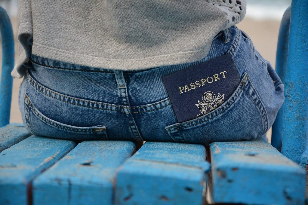 a person sitting on a sandy seat with a passport in their back pocket getting ready for their inexpensive trip to europe