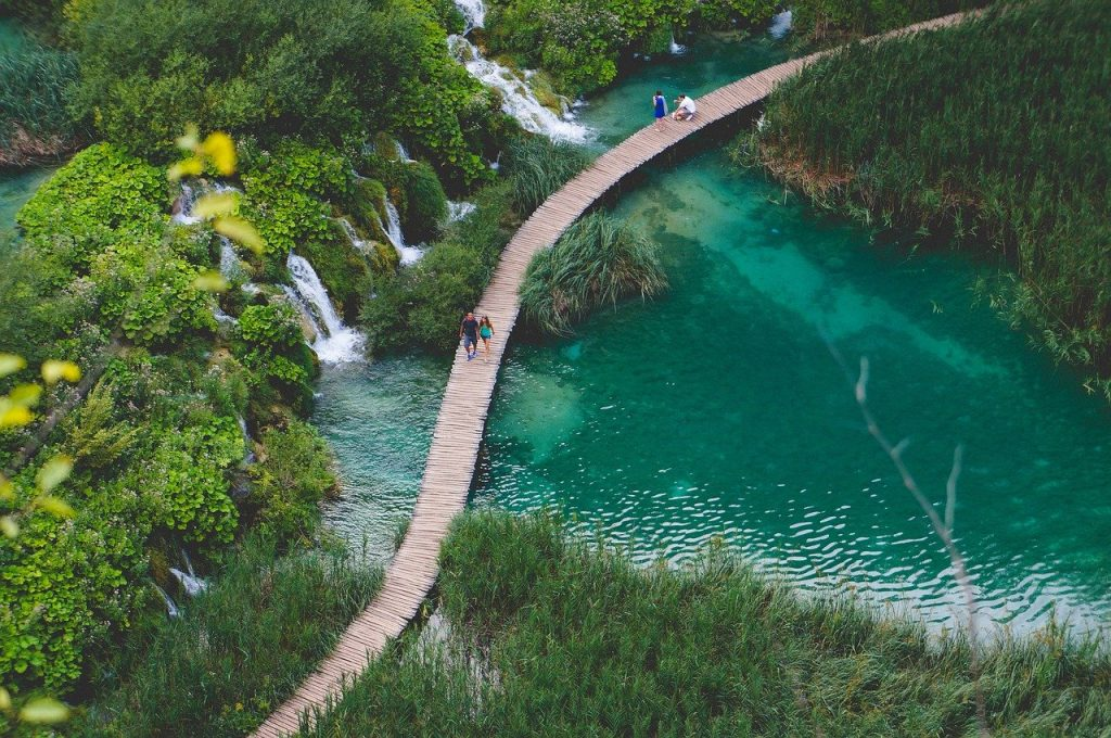 A man and a woman walk across a wooden bridge on top of one of the Plitvice Lakes in Croatia. A backpackers dream for amazing landscape and inexpensive for people looking for cheap european vacations