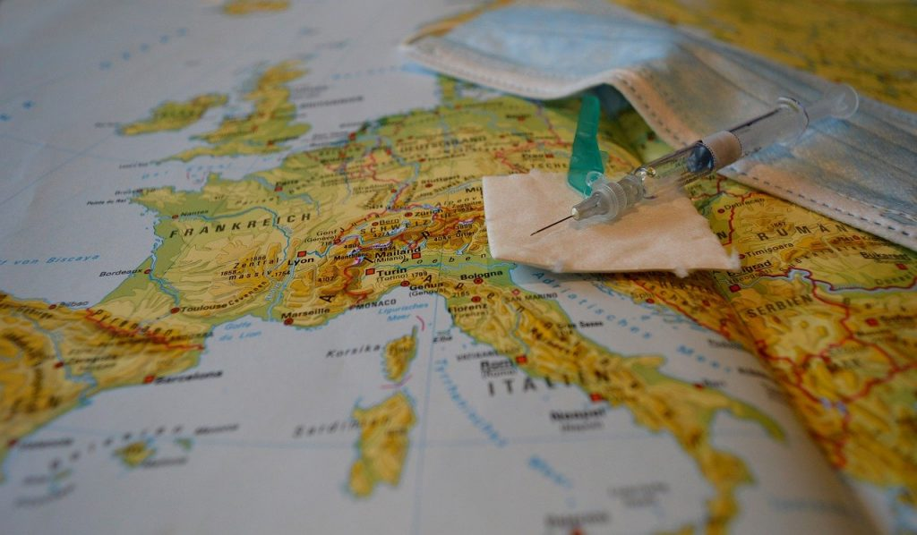 A map of Europe with a covid vaccine and mask laying on top of the map representing the new travel requirements for traveling to Europe.