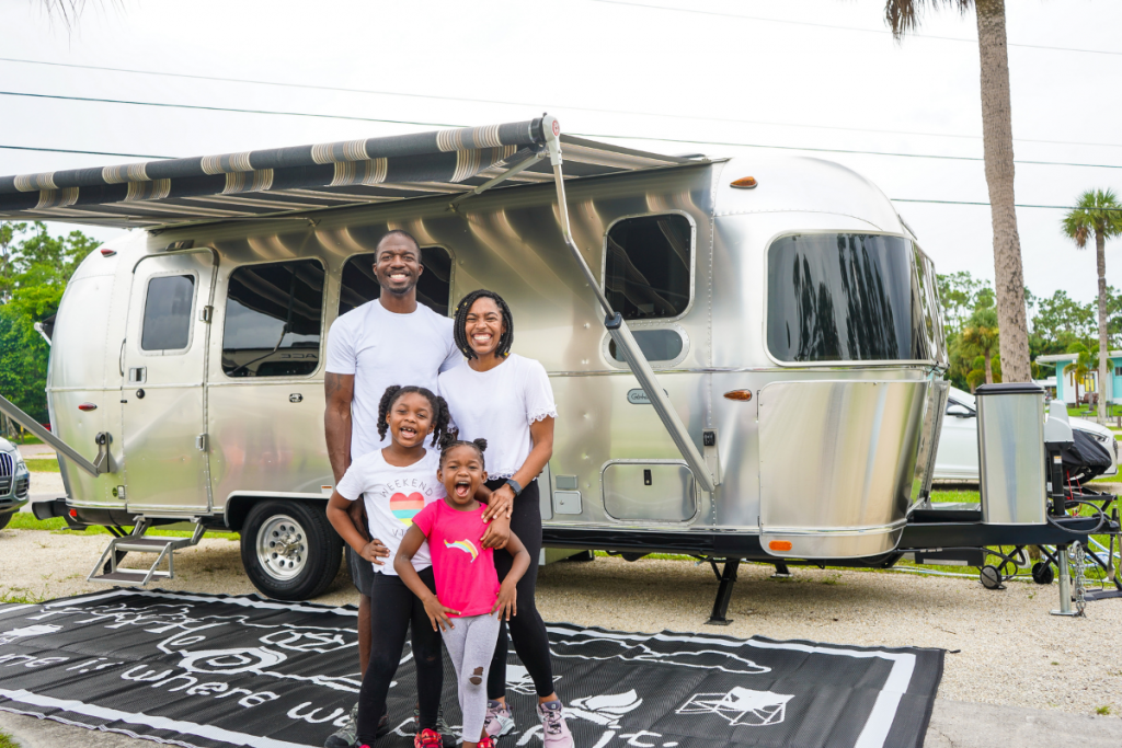 family standing outside of an RV smiling after reaching their destination using RV Apps