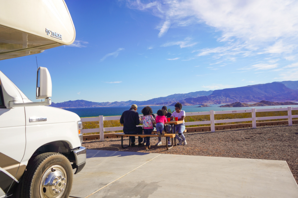 Family is sitting, having a picnic with a lake behind them and their RV parked in front of them.