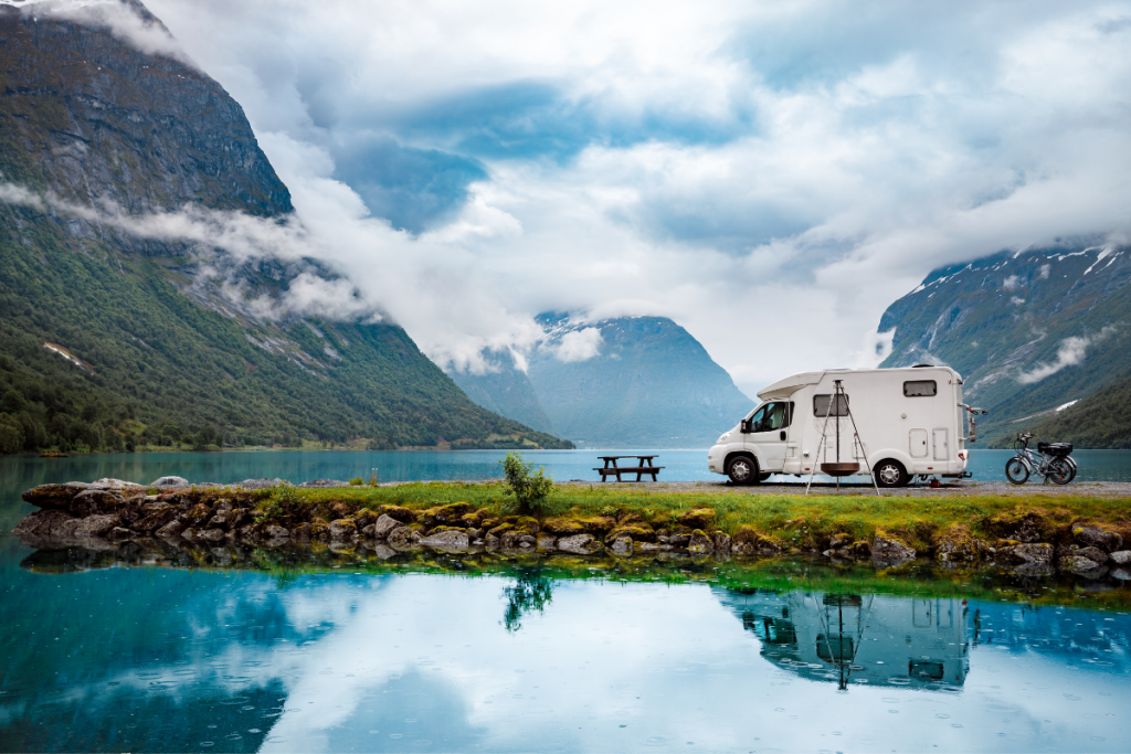 Best RV travel app for boondocking. A motorhome sits on a land bank surrounding by turquois water.