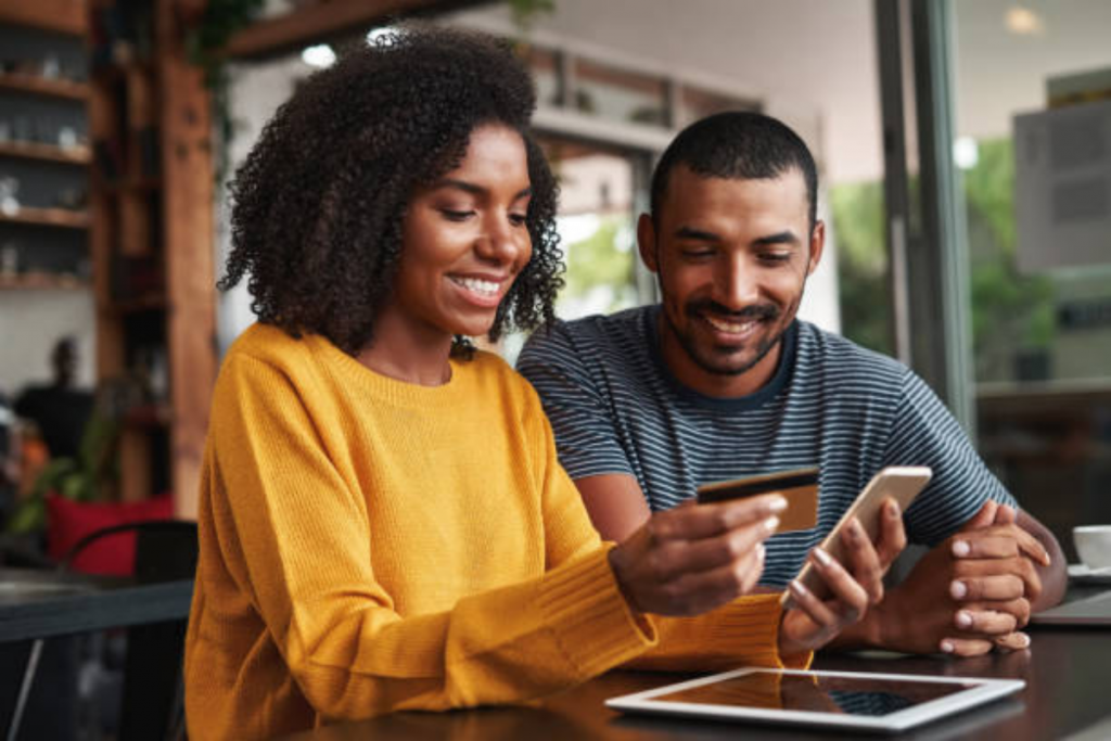 women with credit card in hand along with phone with man sitting next to her