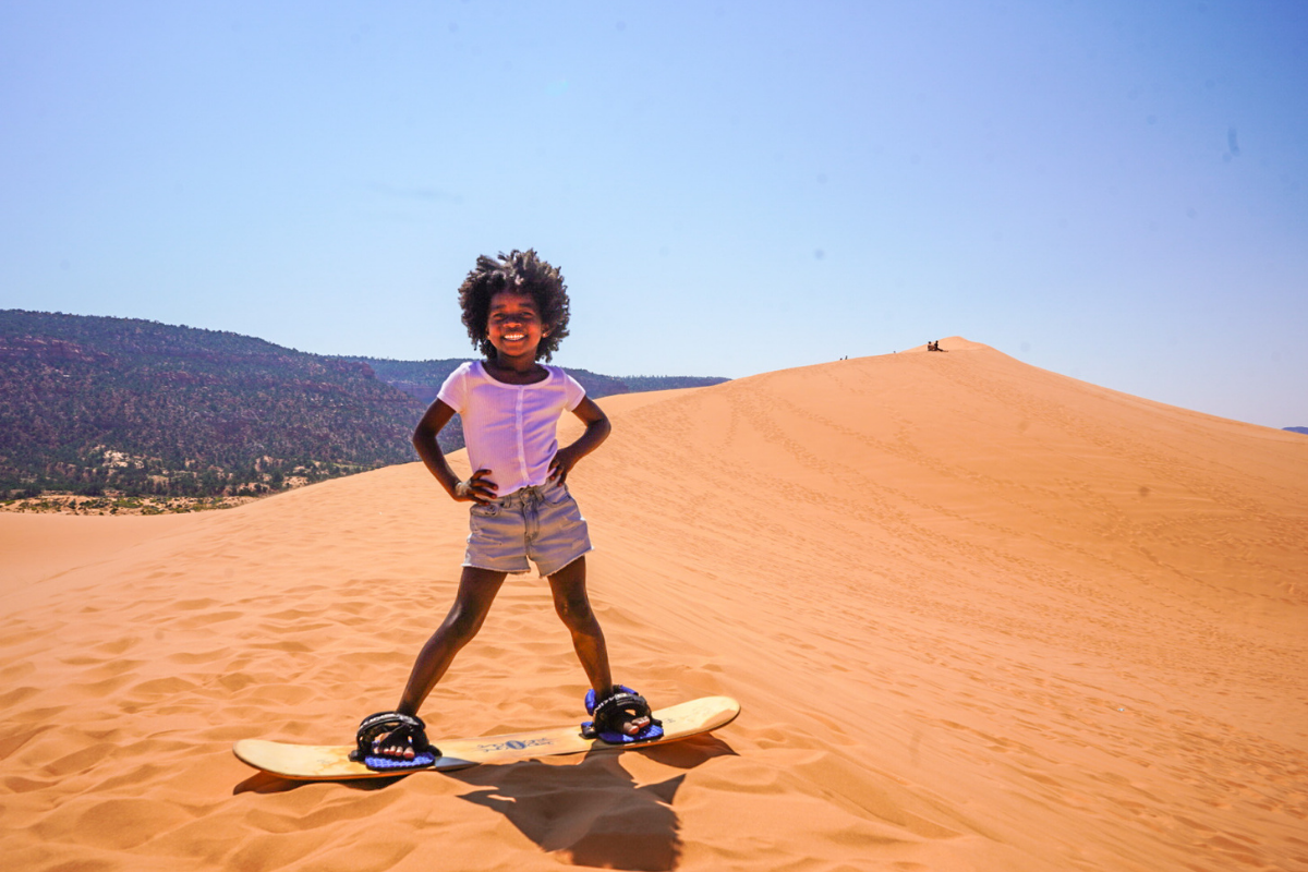 girl on sand board in coral pink sand dunes